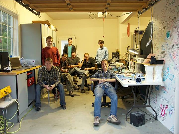 FIGURE 9. The founding team of Planet Labs in the garage with a Dove satel- lite. From left to right: Robbie Schingler, Chris Boshuizen, Nato Saichek, Mike Vlahos, Mike Safyan, Will Marshall, Matt Ferraro, and Ben Howard.